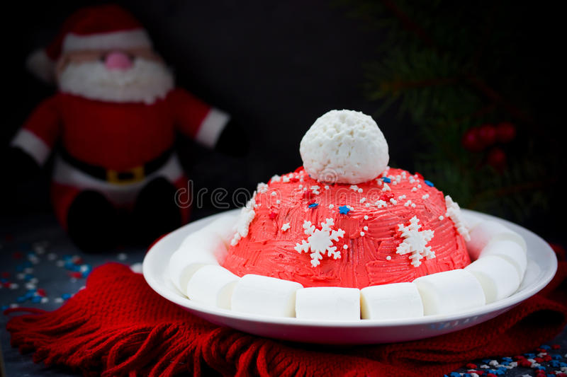 Santa hat Christmas cake. Winter hat cake with traditional ornament decoration. New Year dessert, Christmas treat for kids, Chris royalty free stock images