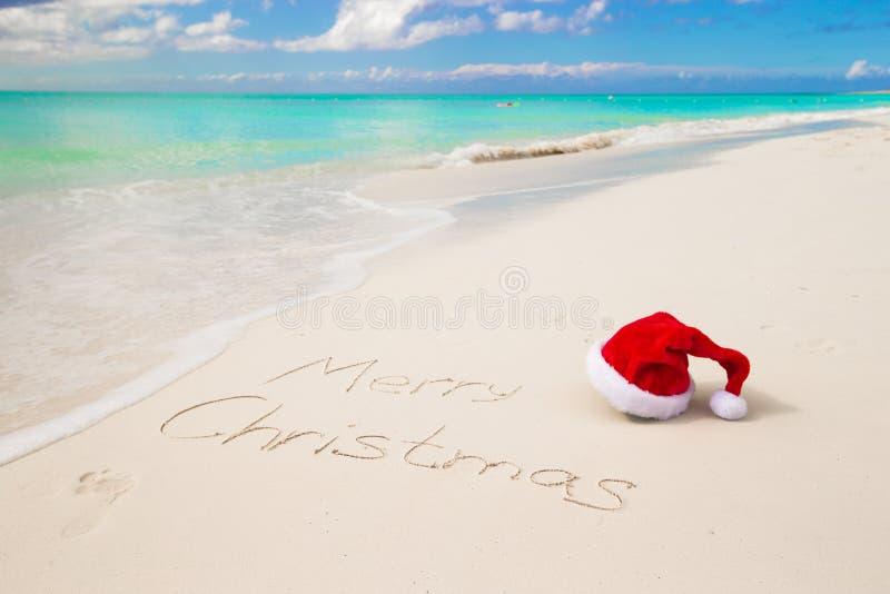 Santa Hat en la playa arenosa y la Feliz Navidad fotos de archivo libres de regalías