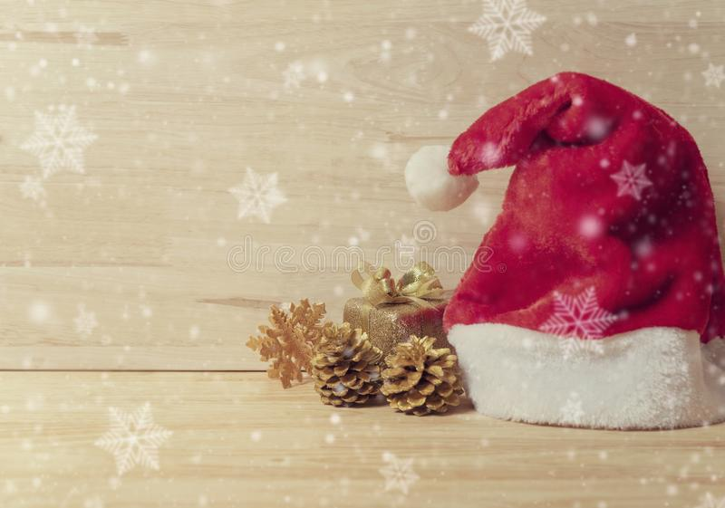 Santa hat and golden pine cones glittered christmas and gift box decoration on wood table background. copy space royalty free stock photography
