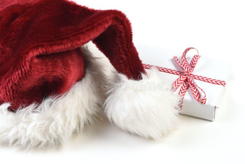 Santa Hat su bianco con un piccolo regalo avvolto immagini stock