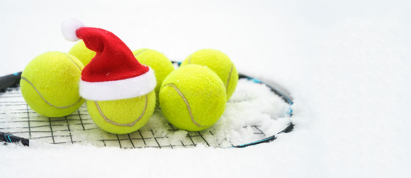 Santa hat on tennis ball, set of tennis balls on racket on white snow winter background. Merry Christmas and New year concept with royalty free stock photos