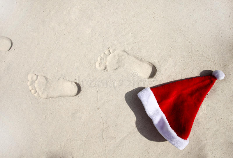 Santa hat and trace on a beach royalty free stock image
