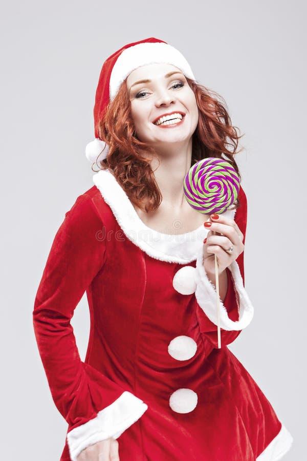 Santa Helper d'une chevelure rouge caucasienne de attirance heureuse avec le bonbon à couleur photo stock