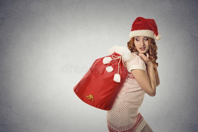 Santa helper girl carrying big red christmas sack full of gifts royalty free stock photo