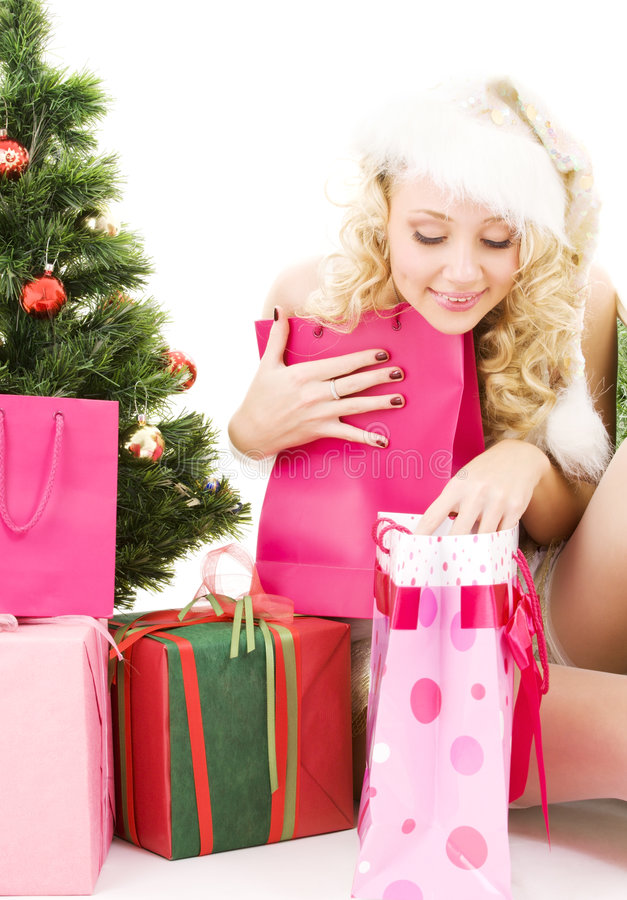 Santa helper girl with gifts and christmas tree stock images