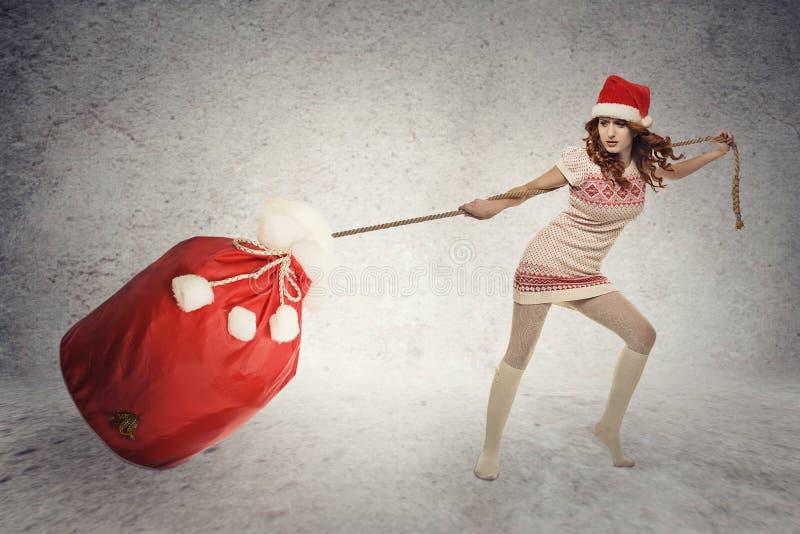 Santa helper girl pulling heavy christmas sack stock photography