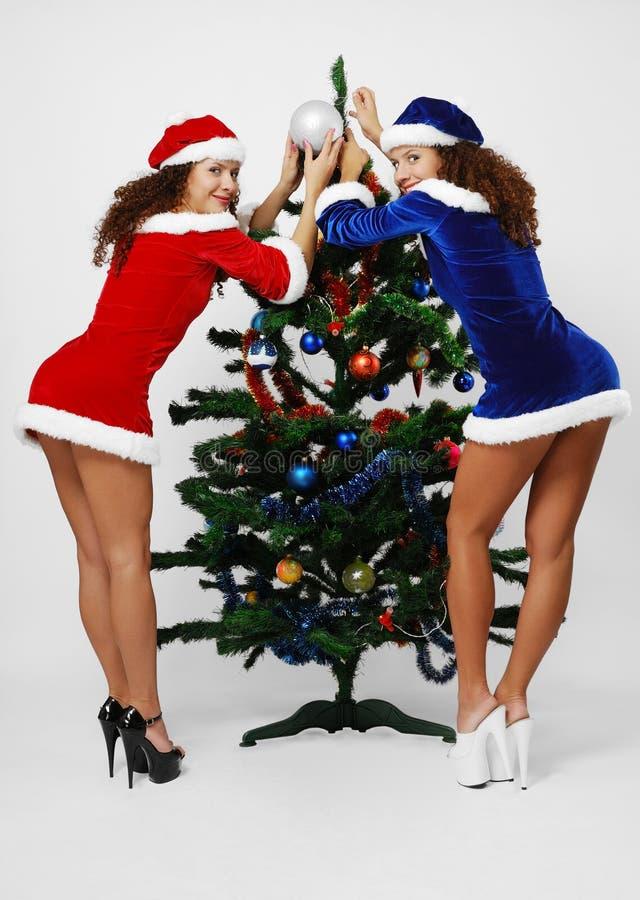 Santa heureuses décorant l'arbre de Noël. photographie stock libre de droits