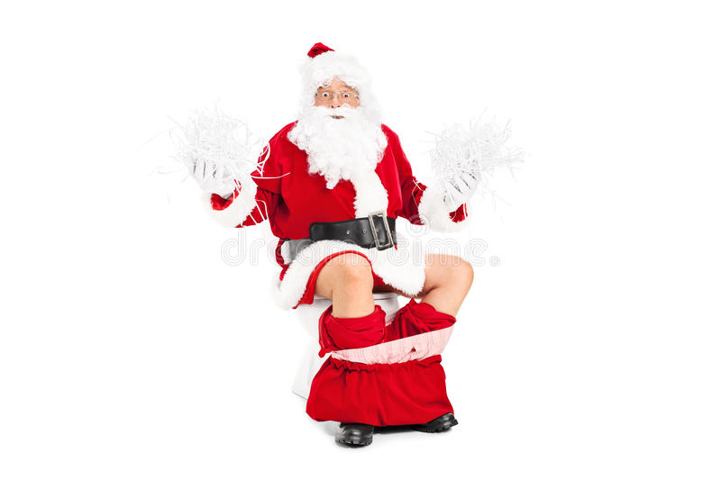 Santa holding bunch of shredded paper on a toilet stock images