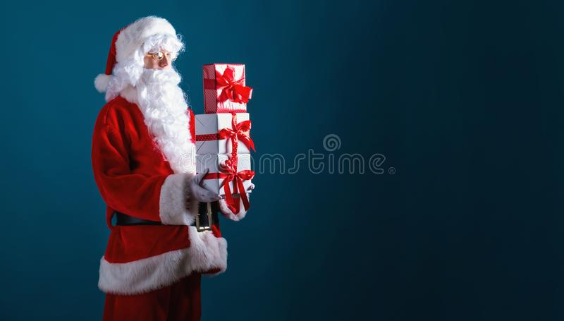Santa holding Christmas gift boxes stock photography