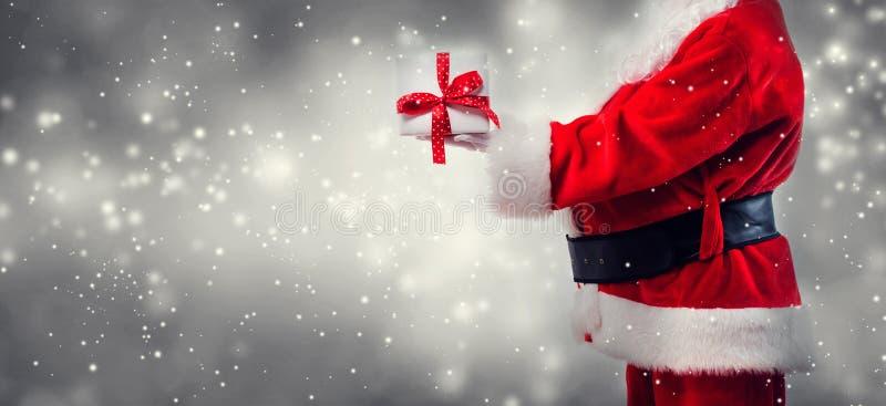 Santa holding a Christmas gift stock photo