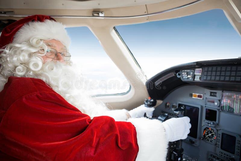 Santa Holding Control Wheel In-Cockpit von privatem stockbilder