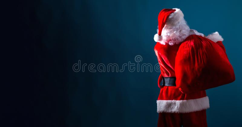 Santa holding a red sack. On a dark blue background royalty free stock photos