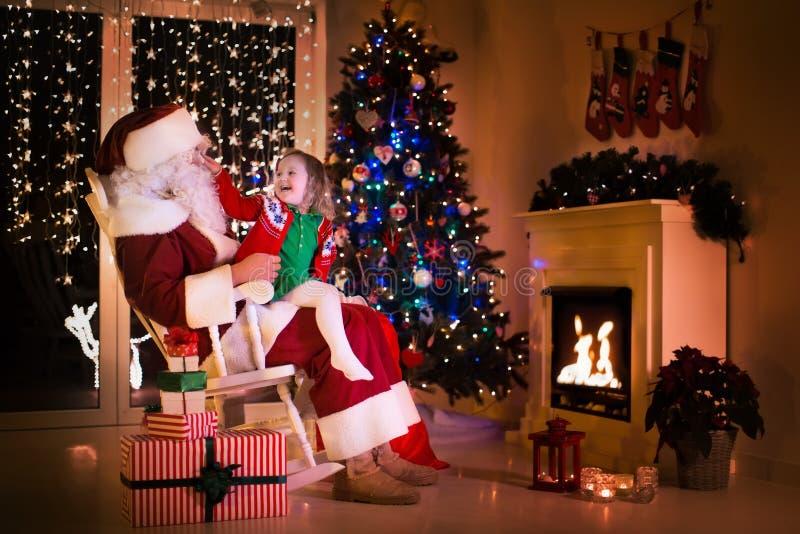 Santa i mała dziewczynka pod choinką zdjęcia stock