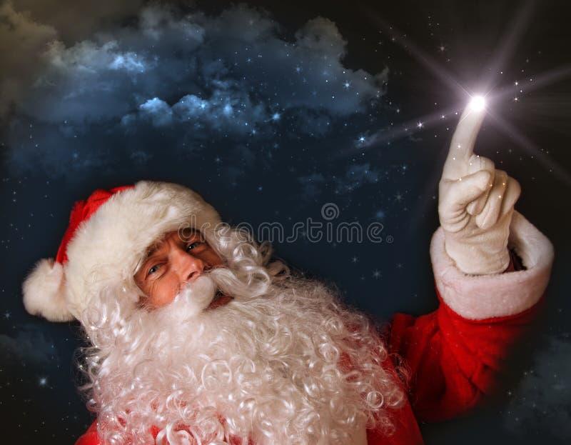 Santa indiquant avec la lumière magique le ciel photos libres de droits