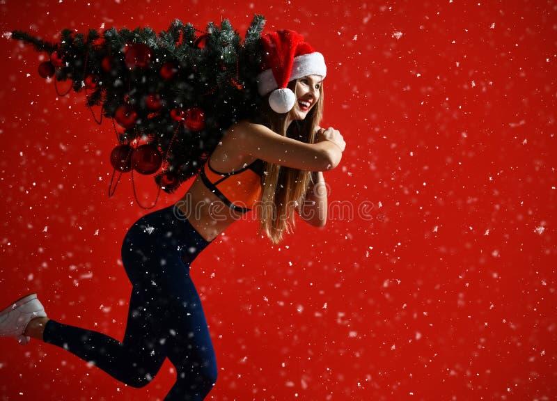 Santa kapeluszowa Bożenarodzeniowa sportowa kobieta trzyma xmas drzewny na jej ramionach Zwycięzca energia on czerwony tło Ja ` s zdjęcia stock