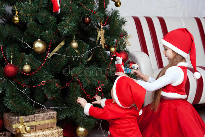 Santa kids decorate a Christmas tree. Christmas and New Year's eve concept stock photography