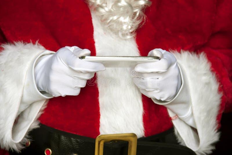 Santa Klaus med listan på iPad arkivbilder