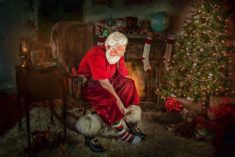 Santa Klaus putting on his boots royalty free stock photos