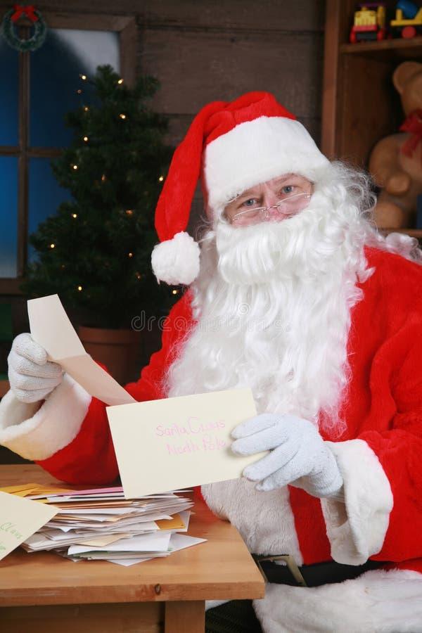 Santa lê seu correio foto de stock