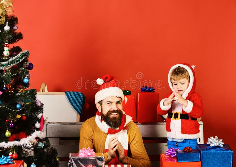 Santa and little assistant among gift boxes near fir tree. Christmas family opens presents on red background. Man with beard and smiling face rub hands in stock images