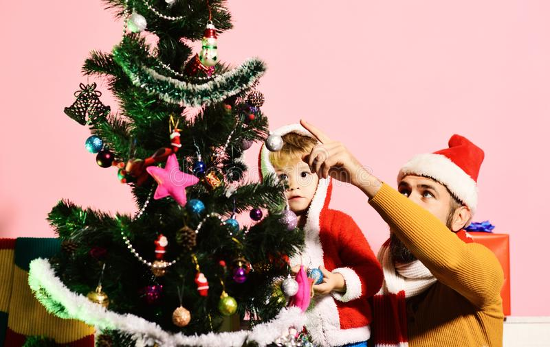Santa and little son stand near Christmas tree. stock photo