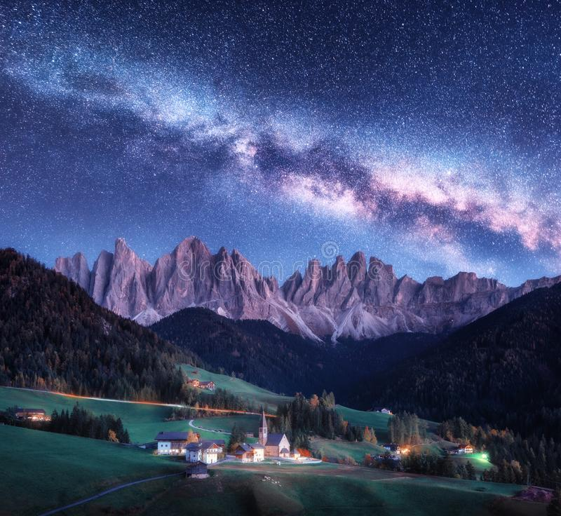 Santa Maddalena and Milky Way at night in autumn in Italy. Starry sky with milky way over St. Magdalena and mountains. Village with houses, church, green stock photos