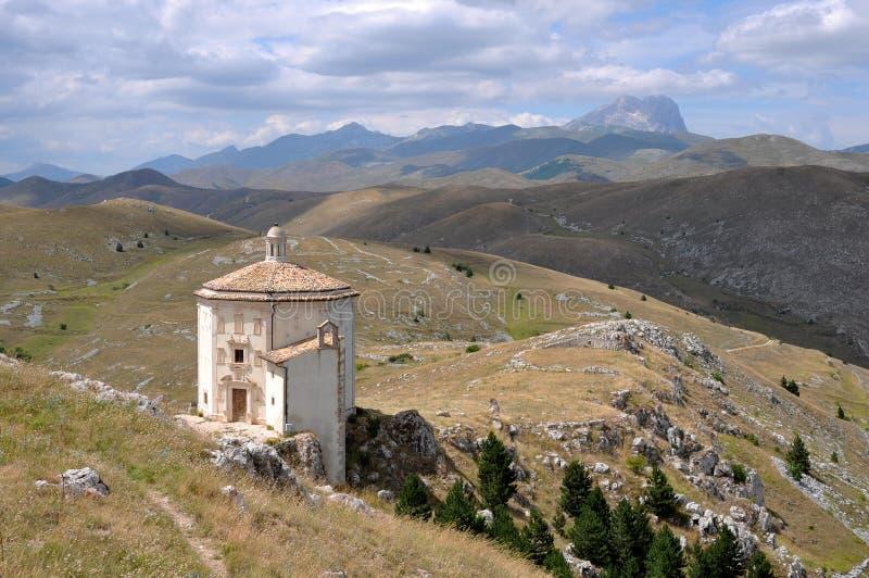Santa maria church and laga mountains. Ancient church in barren landscape of apennines high mountains stock photos