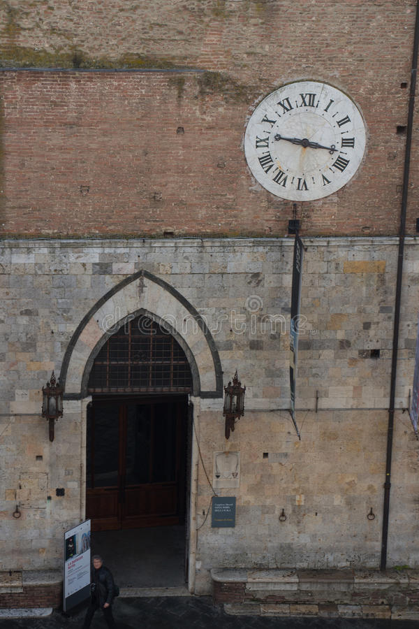Santa Maria della Scala entrance and ancient clock 1643 AD with only hours hand. Siena, Tuscany, Italy. stock photos