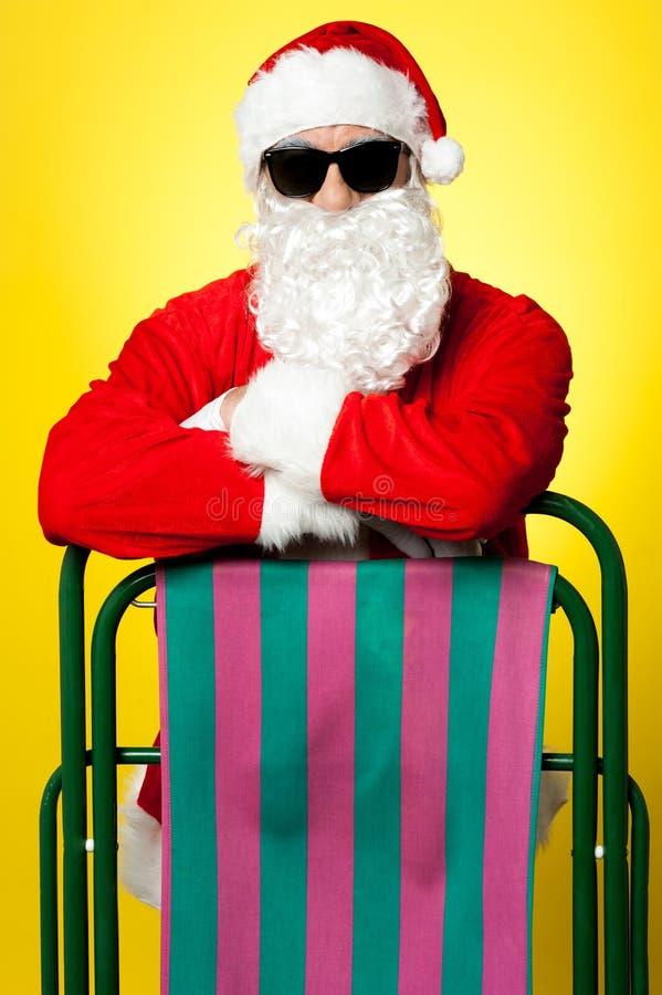 Santa masculina à moda que levanta com um deckchair fotografia de stock royalty free
