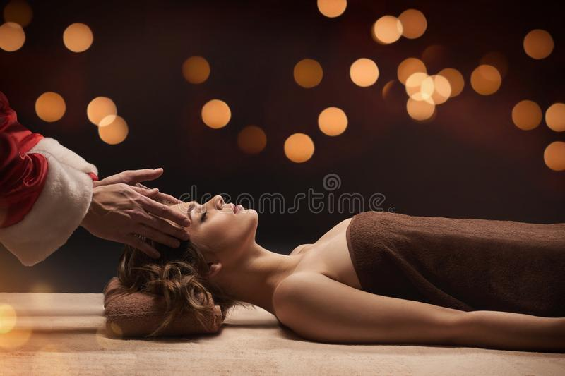 Santa masseur makes SPA treatment for young beautiful woman. stock photos