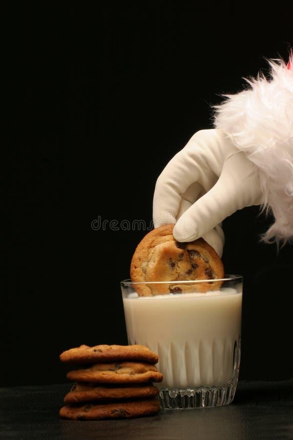 Santa mergulha um bolinho no leite fotos de stock royalty free