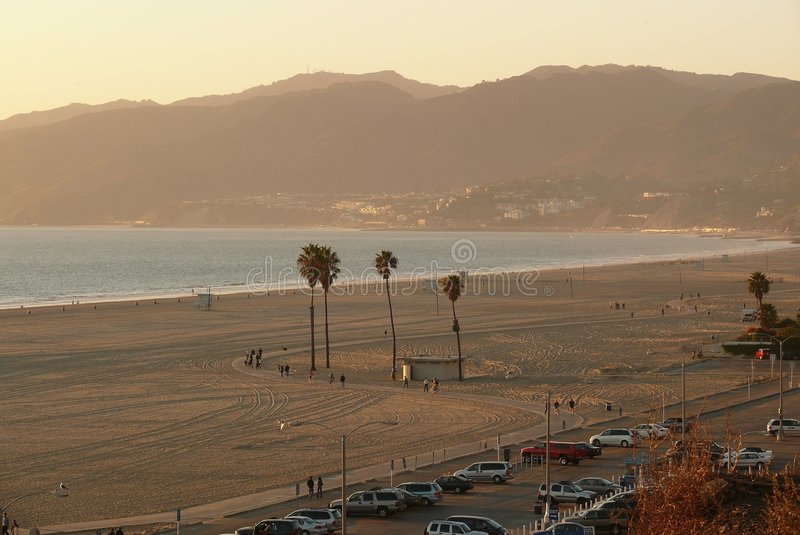 Santa Monica Beach. Bike trail on the beach at Santa Monica. Palm trees, and few people walk and bike enjoying the late afternoon sun stock photos