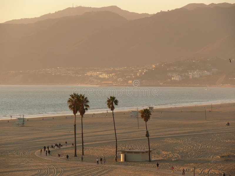 Santa Monica Beach. Bike trail on the beach at Santa Monica. Palm trees, and few people walk and bike enjoying the late afternoon sun royalty free stock images