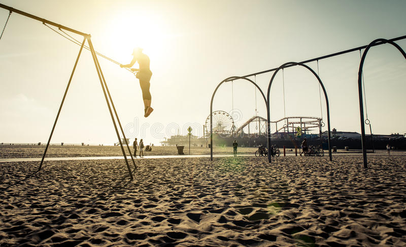 Santa monica beach. silhouette of a woman going up with the swing. Concept about traveling,united states and people stock images