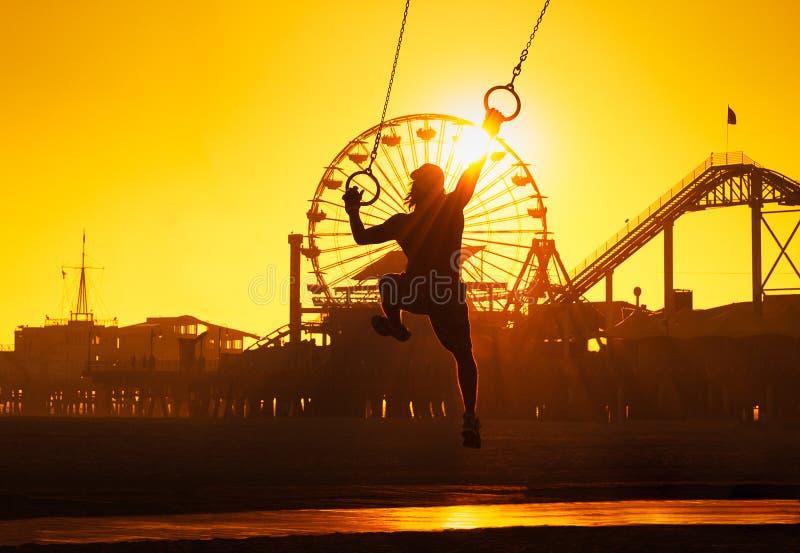 Santa Monica Beach sunset. Silhouette of a man in a baseball cap swinging on rings near the Pier on the beach at Santa Monica, California stock photo
