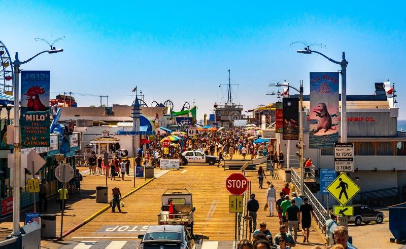Santa Monica Pier, Beeld met mensen die bij de pijler met het eind van Route 66 lopen Het pretpark is een beroemde aantrekkelijkh stock afbeeldingen