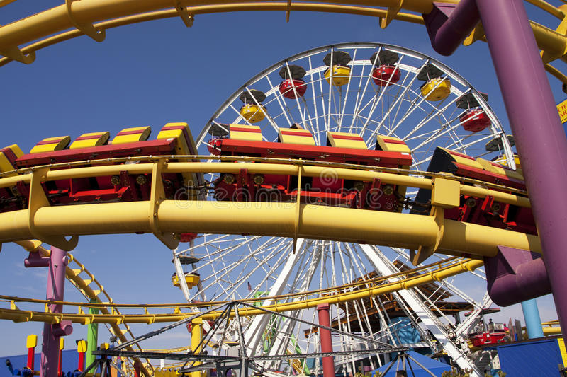 Santa Monica Pier Carnival Amusement Thrill Rides. Colorful ferris wheel amusement thrill ride and roller coaster track at the Santa Monica Pier on the Pacific royalty free stock image