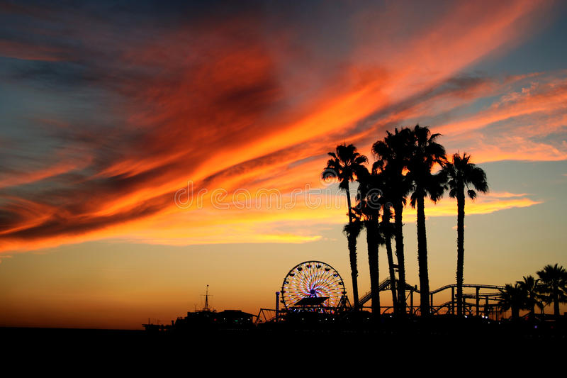 Santa Monica Pier and Palm Trees at Sunset. Shadows of palm trees against a sunset with Santa Monica Pier, ferris wheel and dramatic clouds in the background royalty free stock images