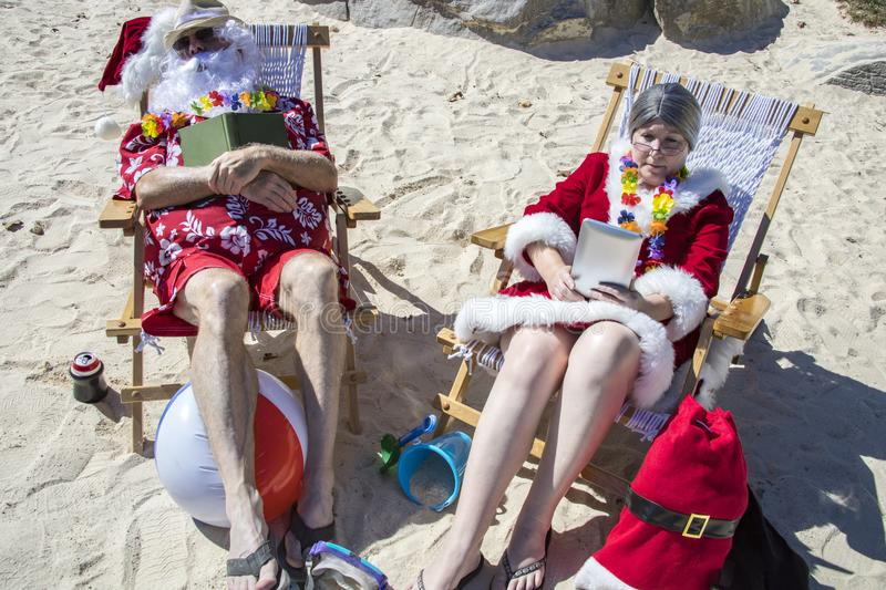 Santa and Mrs Claus reading books and napping on beach. Santa Claus in red swimming trunks and Hawaiian shirt lounging on sandy beach with Mrs Claus reading and stock photo