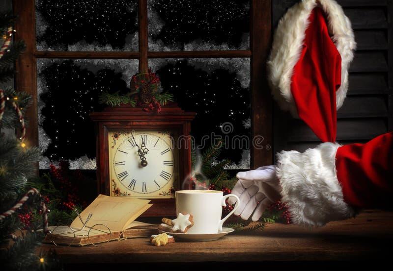 Santa Picking Up Hot Drink na meia-noite imagem de stock royalty free