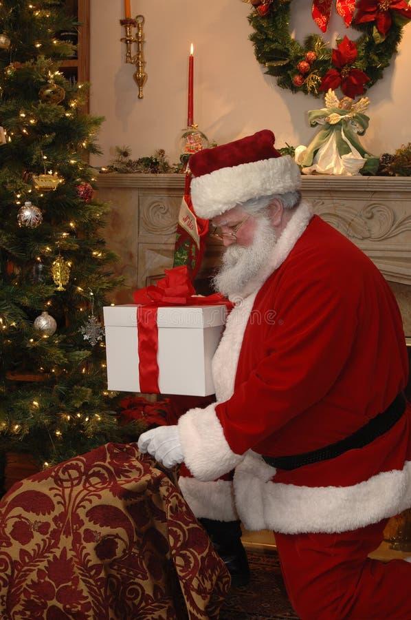 Santa Placing a Gift royalty free stock photos