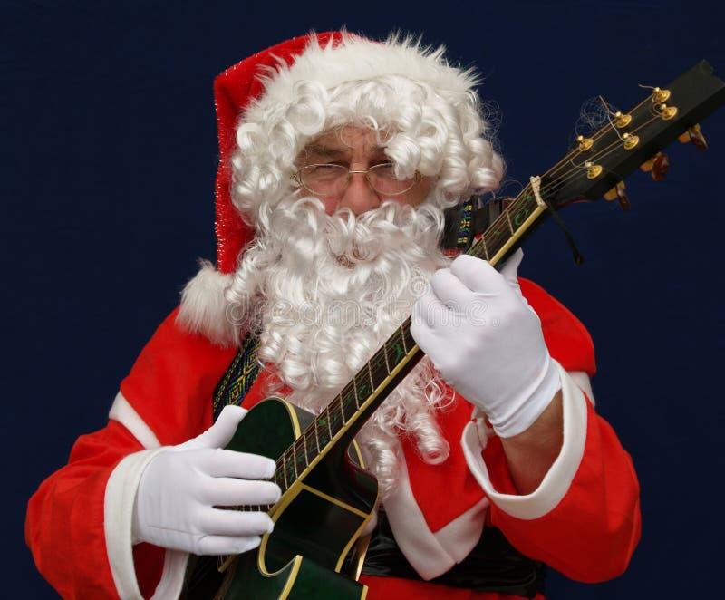 Santa playing christmas carols stock photos