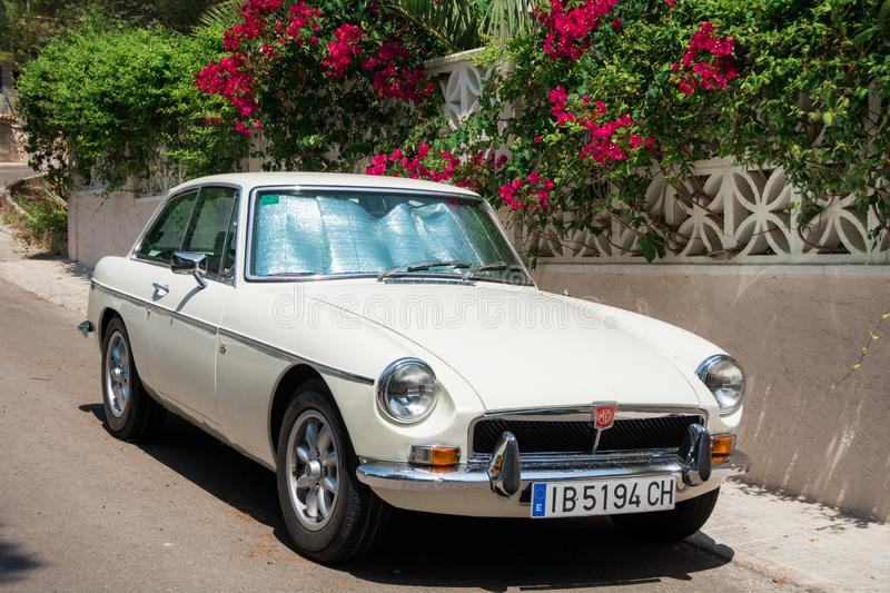 Retro car MG BGT is parked near a wall with flowers and palm leaves. stock image