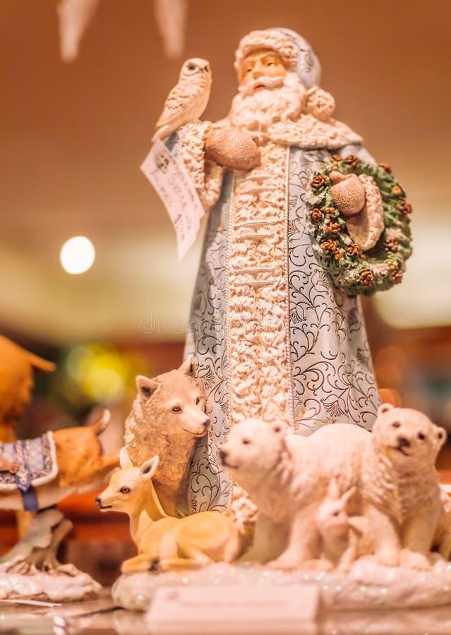 Santa Porcelain Statue mit wild lebenden Tieren um seine Füße lizenzfreie stockfotos