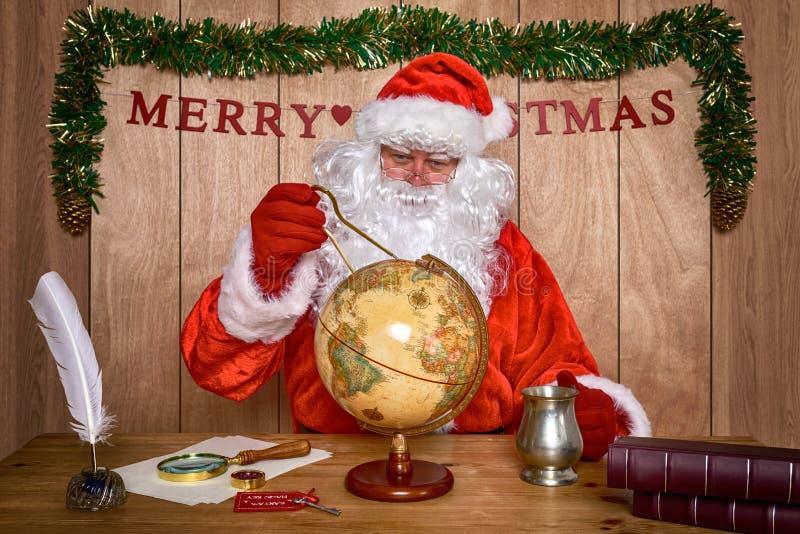 Santa prévoyant son itinéraire de la livraison. photographie stock