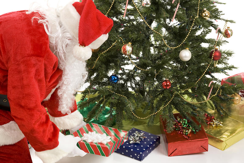 Santa Puts Gifts Under Tree stock image