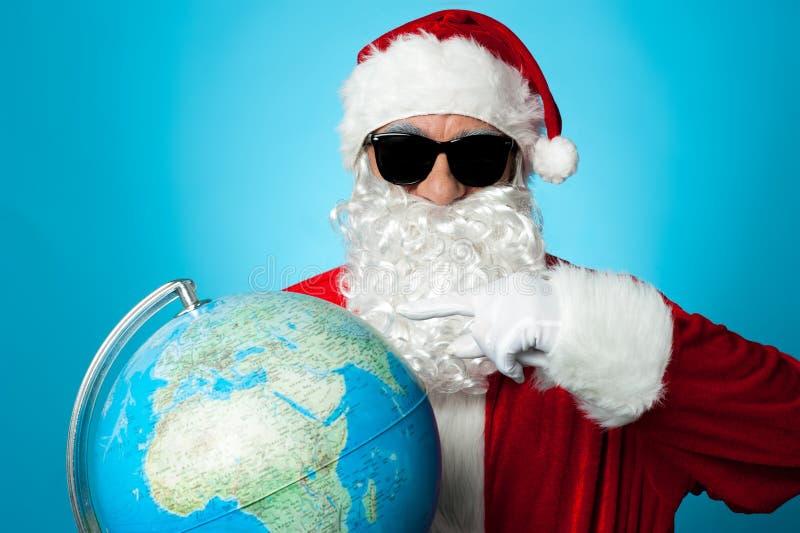 Santa que aponta no mapa do globo fotografia de stock