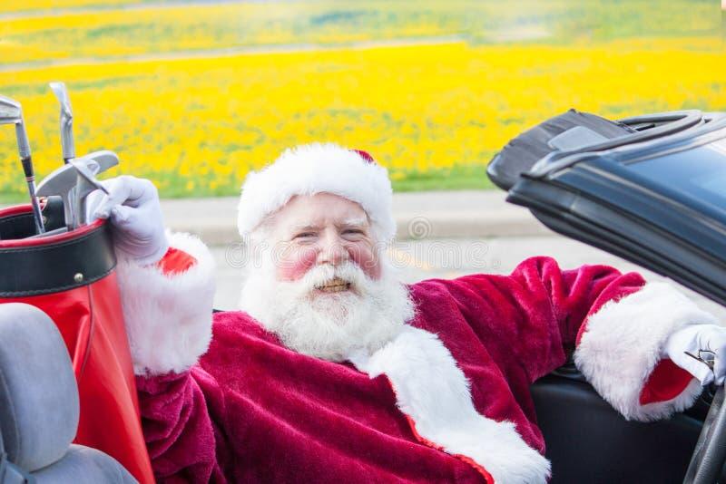 Santa que conduz o convertible com clubes de golfe fotografia de stock
