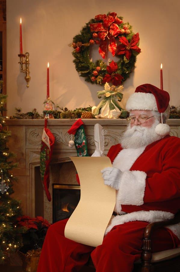 Santa que controla la lista foto de archivo