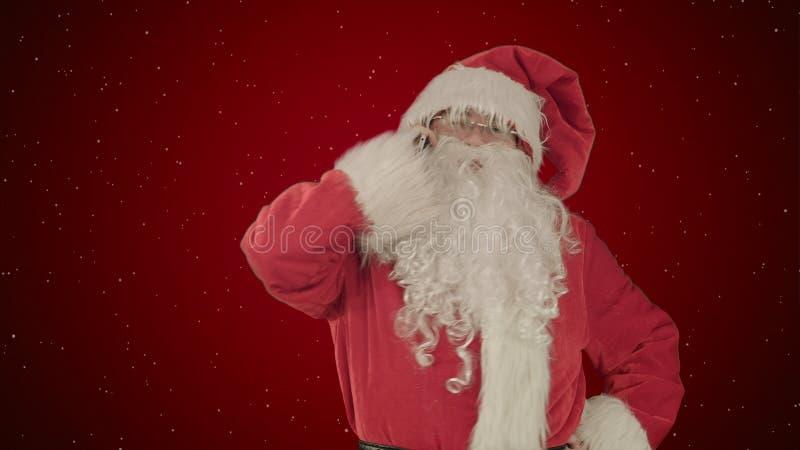 Santa que fala em seu telemóvel com um olhar surpreendido em sua face no fundo vermelho com neve fotos de stock
